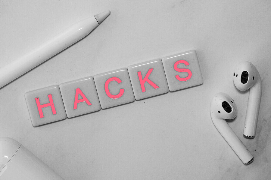"""Scrabbles tiles saying """"hacks"""" on table next to wireless headphones"""